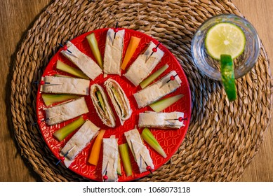 top view of a plate with healthy appetizers and a glass of lemon water