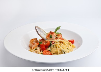 Top view Plate of Italian Seafood Pasta with clam, shrimps, cherry tomatos and basil decorated with shell mussel isolated on the white background