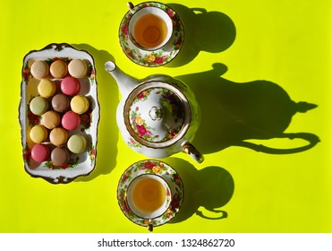 Top view of a plate with macaroons, a tea pot and tea cups in a yellow background with shadow