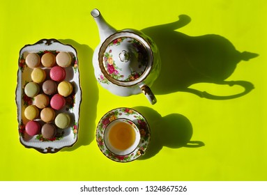 Top view of a plate with macaroons, a tea pot and tea cup with saucer in a yellow background