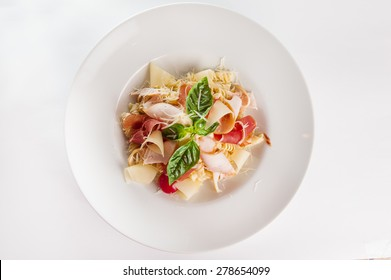 Top view Plate of meat Pasta with ham and  prosciutto slices decoratred with cherry tomatos, parmesan cheese and basil on the white plate isolated