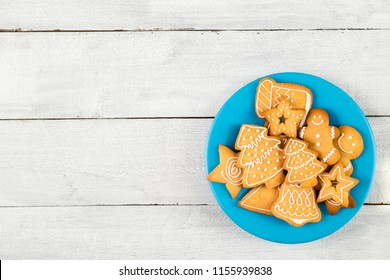 Top view of a plate of nicely decorated Christmas cookies on white wooden background. Selective focus on the cookies
