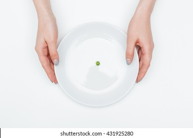 Top view of plate with one small green pea holded by hands of young woman over white background