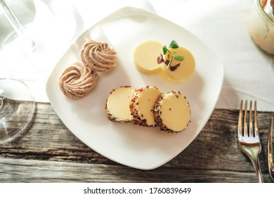 Top view of plate with several slices of flavored butters laying on wooden table with white tablecloth. Celebration, birthday or wedding concept. Image.