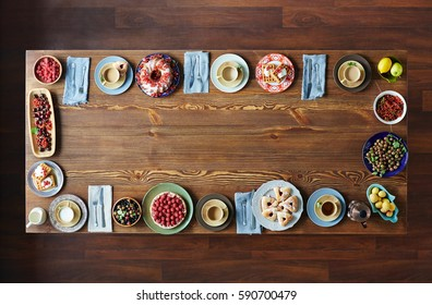 Top view of plates with delicious homemade pastry, garden berries, fruits, cups and cutlery placed on large wooden table