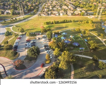 Top view playground near residential neighborhood with overhead power lines in Carrollton, suburbs Dallas, Texas, USA. Recreational green space sizable synthetic turf, covered picnic spot at sunset