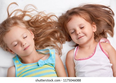 Top view of pleased attractive small girls or sisters smile together, sleep in bed, lie closely to each other, see pleasant dreams, dressed in nightwear. Children, relationship and friendship concept
