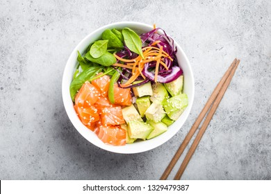 Top view of poke bowl with fresh raw salmon, avocado, rice, spinach, vegetables. Traditional Hawaiian dish on rustic stone background. Healthy and clean eating concept. Poke with slices of raw fish