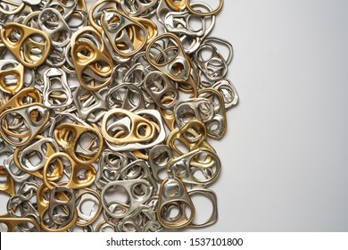 Top view of pool or many of gold and silver metal ring pull or pull tab lid for bottle or can opener on white background , recycle or eco and environmental friendly concept ,with copy space
