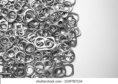 Top view of pool or many of silver metal ring pull or pull tab lid for bottle or can opener on white background , recycle or eco and environmental friendly concept with copy space