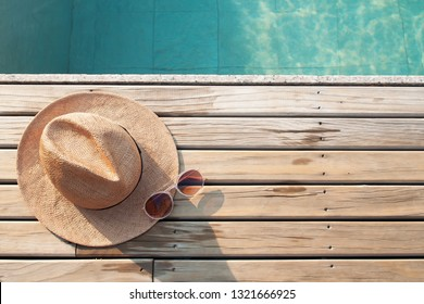 Top view of poolside, sun hat and sunglasses on wooden floor with copy space for text or word advertising