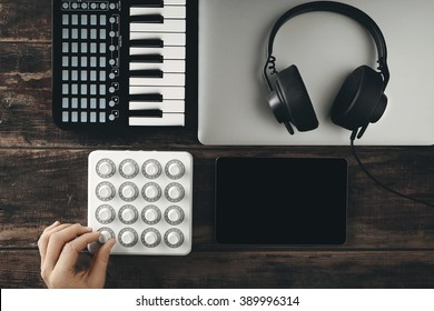 Top view portable travel music production set midi mixer control piano keyboard smartphone tablet retina laptop black dj headphones with leather earpad long twisted cort on aged table Hand twist knob