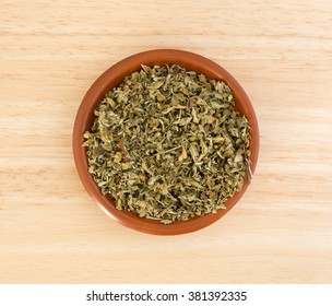 Top view of a portion of damiana leaf in a small bowl on a wood counter top.