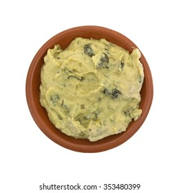 Top view of a portion of freshly made packaged spinach hommus in a small bowl isolated on a white background.