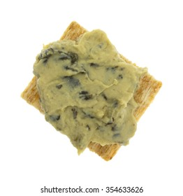 Top view of a portion of spinach hommus on a whole grain cracker isolated on a white background.