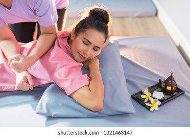 Top view portrait of Asian attractive tan girl relax in spa. Body care therapy by Thai massage. Happy woman massaged back by professional with candle and Plumeria on bed.