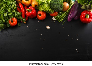top view portrait of Assortment of fresh raw vegetables on black wooden background with blank space