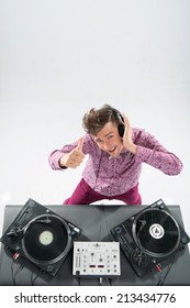 Top view portrait of emotional handsome dj, stylish look and haircut with headphones spinning vinyl records on turntable isolated on white background