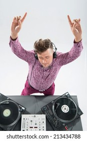 Top view portrait of emotional handsome dj in stylish look and haircut with headphones lifting fingers standing by turntable isolated on white background