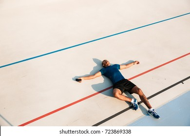 Top view portrait of an exhausted young african fitness man resting while lying on a ground at the track field outdoors