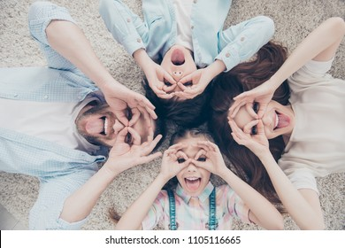 Top view portrait of foolish comic family with two kids lying on carpet making eyewear with fingers gesturing tongue-out happy together. Freetime daydream concept