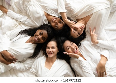Top view portrait of happy multiracial millennial girls in bathrobes lying on bed smiling posing at bridal shower, overjoyed diverse female friends have fun celebrate bachelorette hen party at home