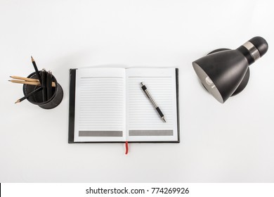 top view portrait of notebook, table lamp, and stationary at working space on white background
