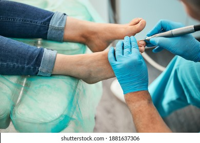 Top view portrait of patient legs on medical chair while doctor chiropodist using electrical modern machine for apparat medicine pedicure in beauty center