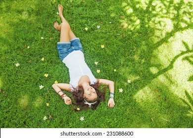 top view portrait of a pretty young woman relaxing on a grass
