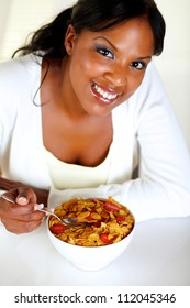 Top view portrait of a smiling young woman looking at you and having healthy breakfast at soft colors composition