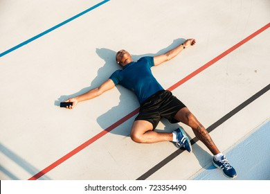 Top view portrait of a tired young african fitness man resting while lying on a ground at the track field outdoors