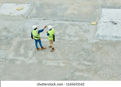 Top view portrait of two workers standing on concrete floor of construction site and planning project, copy space background