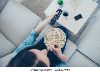 Top view portrait of woman in denim outfit sitting on sofa indoor searching movie using remote controller having bucket with pop corn sitting in living room
