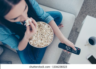 Top view portrait of woman in jeans outfit sitting with crossed legs on sofa searching movie using remote controller having bucket with pop corn sitting in living room