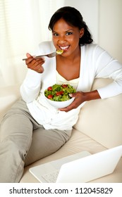 Top view portrait of a young female eating healthy salad and looking at you while is sitting on couch in front of her laptop