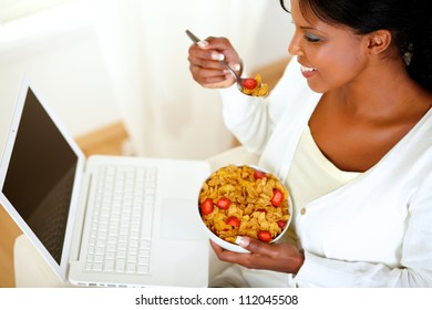 Top view portrait of a young woman looking to laptop while is having healthy breakfast