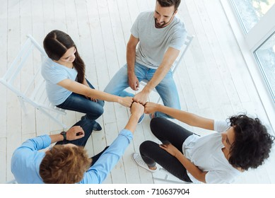 Top view of positive delighted people sitting in the circle