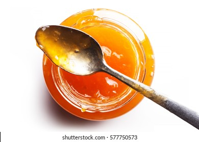 Top view of pot of peach jam with spoon over it and white background