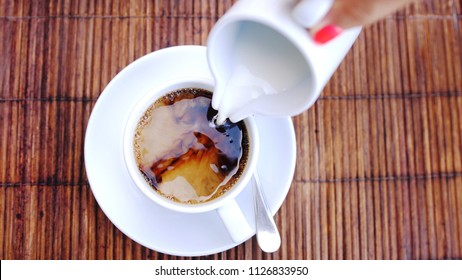 Top of view of pouring stream milk into a cup of espresso on a wooden table.