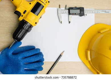 Top view of power drill, pencil, vernier caliper, safety helmet on blank paper
