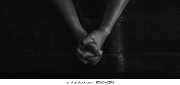 Top view prayer's hand in church on wooden floor, Pastor pray to God on black background, religion concept