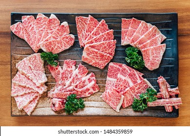 Top view of Premium Rare Slices many parts of Wagyu A5 beef with high-marbled texture on stone plate served for Yakiniku (Grilled Meat).