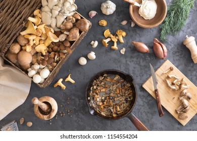 Top view of preparation and frying of edible wild mushrooms, food photo. Mix of chanterelle, portobello, shiitake in Cast-iron pan. Cooking with spices, butter, parsley, onion, leek, garlic.