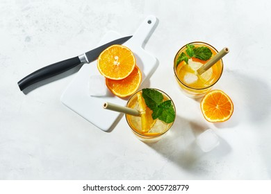 Top view of prepering summer cockteil. Glasses with gin and cold tonic with orange and mint, decorated with slices and with ice cubes on white background and bamboo straw.