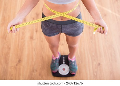 Top view of pretty slim woman with measure around her body is standing on the scales.