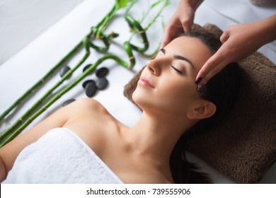 Top view of pretty woman laying in spa salon with closed eyes and relaxed