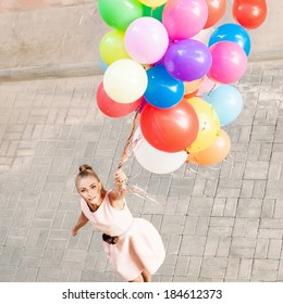 top view of pretty young girl in pink dress holding a bunch of balloons