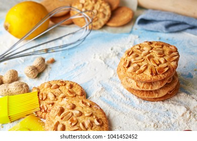 top view of product set for cooking cookies, kitchenware and several round cookies with peanuts on scattered flour on a blue wooden table