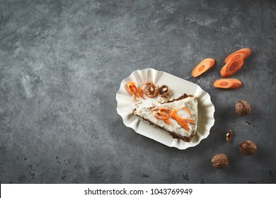 top view of product set on gray concrete table and piece of sliced vegan carrot pie on the paper dish. view from above with copyspace