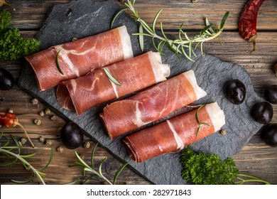 Top view of prosciutto on rustic background